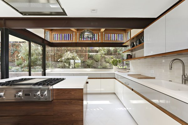 originally covered in colorful tile the kitchen received a monochromatic upgrade with white quartz countertops and new state of the art appliances